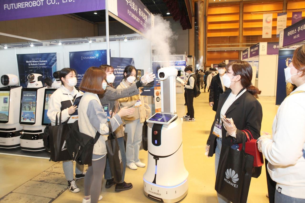 참관객이 퓨처로봇의 AI 방역 로봇을 체험하고 있다.